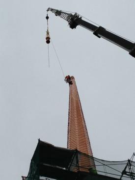 Crane sets spire finial.