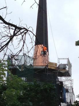 Steeplejack installs copper shingles over original decking.