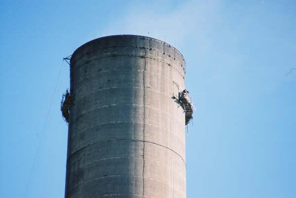 Dunbar on a 500 foot concrete chimney, assembling an engineered scaffold.