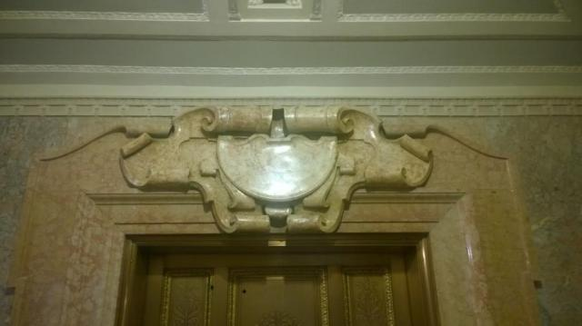 Cast scagliola cartouche over elevator doors, matching the adjacent molded marble surrounds.