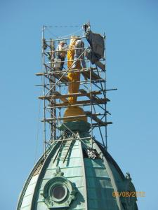 Gilders at work, note scale of the statue. She had never been gilded before, note bare (verdigris) metal.