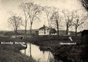 Looking upstream, the monument at the right, around 1900. The area is now much more built up, with both houses and trees.
