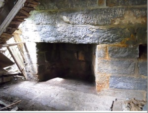 Detail of dressed stone fireplace and hearth, ready for dismantling.
