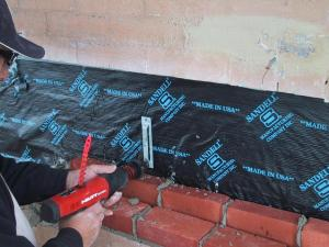 Installation of moisture protection for the steel before closing up the brickwork.
