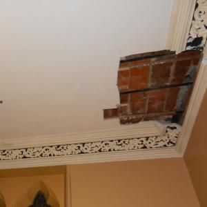 Damage to historic interior plaster by mechanical systems installation.