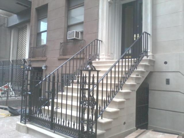 Ornamental iron railing and double gate on brownstone stoop.